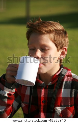 a young boy drinks from a cup at a picnic - stock photo