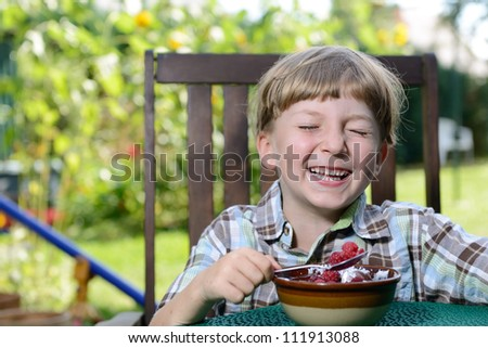 a young boy eating a tasty raspberry with yogurt - stock photo