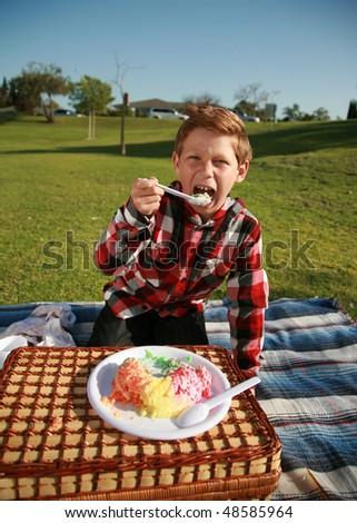 a young boy enjoys jello at a picnic outside at a park - stock photo