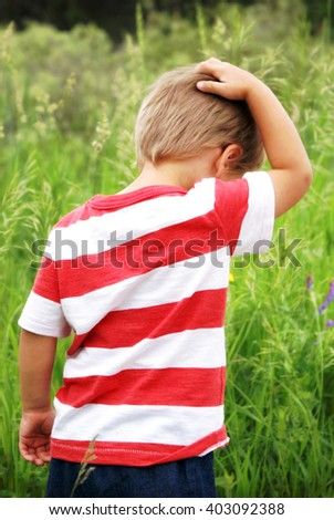A young boy explores the great outdoors while creating some thoughts in this candid image of him scratching his head during his boyhood sense of wonder. - stock photo