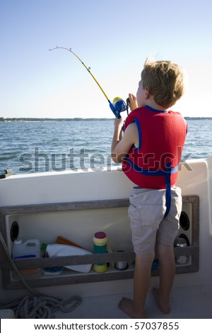 A young boy fishing from a boat. - stock photo