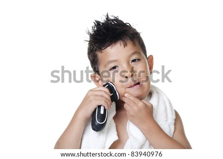 A young boy has fun pretending to shave with an electric razor.