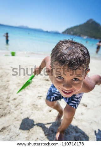 A young boy having fun at the beach whilst on holiday. - stock photo