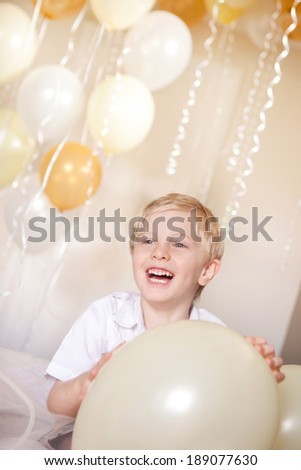 A young boy holding a balloon with balloons in the background.  He is celebrating his birthday.  He he has blonde hair and a happy look on his face - stock photo