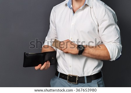 A young boy holding a bank card. Part of the body. Bank account. Muscular body.  - stock photo