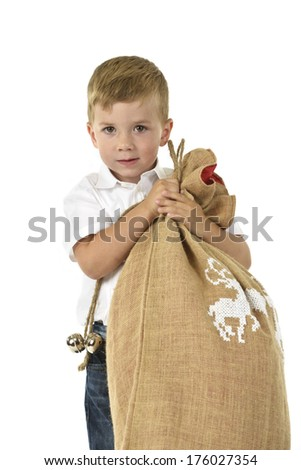A young boy holding a sack full of something. - stock photo