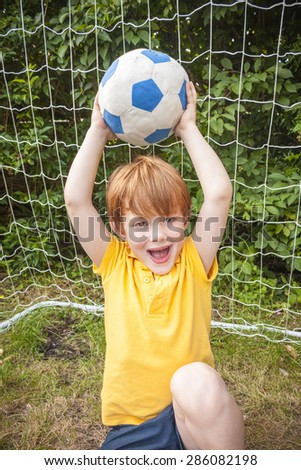 A young boy holding up a football and looking happy in front of a goal - stock photo