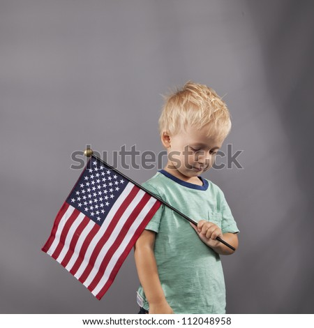 A young boy holds an American flag over his shoulder.