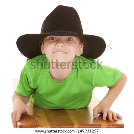 a young boy in a big cowboy hat laying and looking.