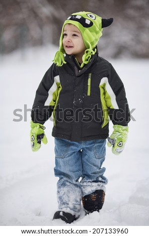 A young boy in a monster hat and gloves walks cheerfully through the snow. - stock photo