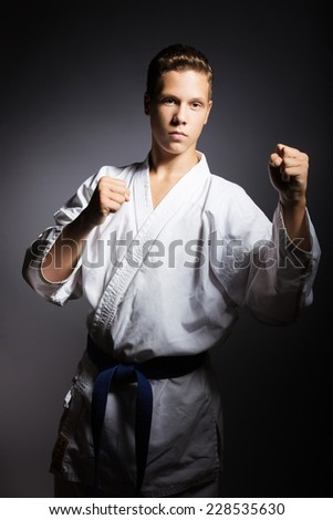 A young boy in a sports kimono in the image judo. Picture taken in a studio on a gray background