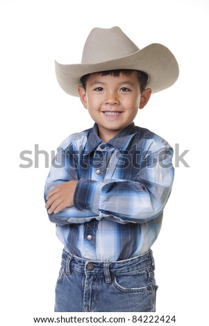 A young boy in cowboy clothes crosses his arms and shows a big smile. - stock photo