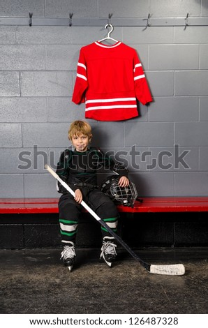 A Young Boy in Dressing Room partially dressed in hockey equipment - stock photo