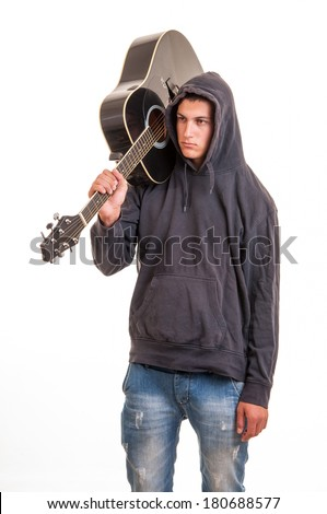A young boy in hoodie standing with his guitar on the shoulder