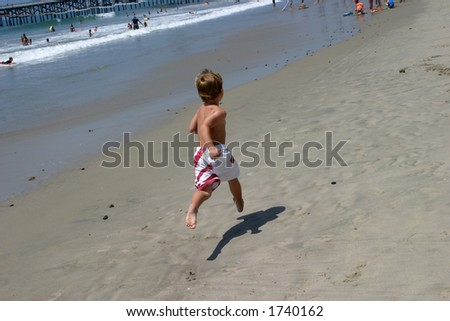 a young boy is airborne while running on the beach