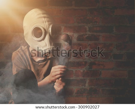 A young boy is holding a dead flower against a brick wall with a gas mask and dangerous gas in the air for a global warming or destruction concept.