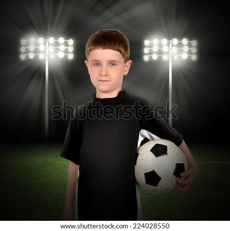 A young boy is holding a soccer ball with a stadium of lights in the background at night for a game or sport concept. - stock photo