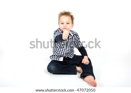 A young boy is holding his thumb up. - stock photo