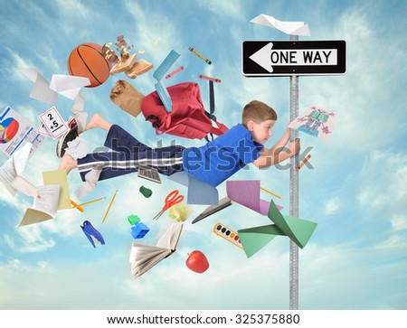 A young boy is holding on to a one way direction sign with school supplies flying around him for an education activity or speed concept - stock photo