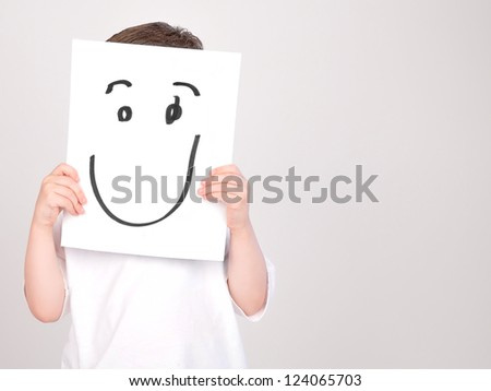 A young boy is holding up a white paper with a drawing of a happy face. Add a message on the copyspace.