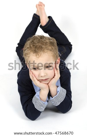 A young boy is looking sad at a white background. - stock photo