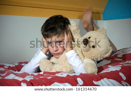 A young boy is lying sad and angry on his bed in his bedroom - stock photo