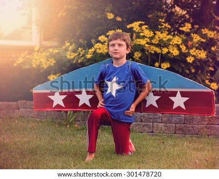 A young boy is pretending to be a pilot with wings and stars in his front yard for an imagination or dream concept. - stock photo