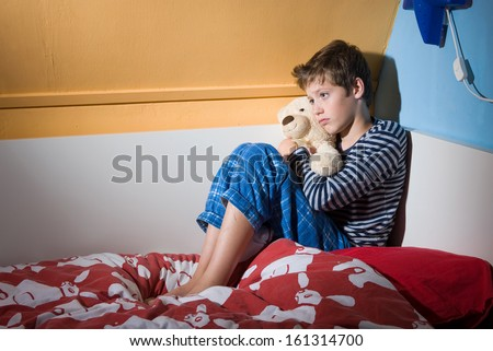 A young boy is sitting afraid and depressed on his bed in his bed room - stock photo