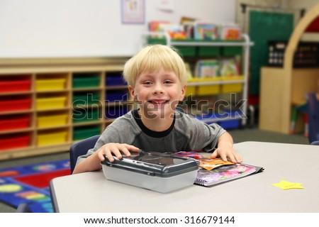 A young boy is sitting at his desk on his first day of school in his kindergarten classroom.