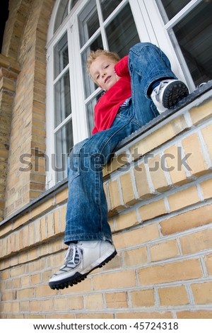 A young boy is sitting at the wall. - stock photo