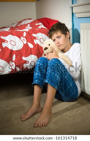 A young boy is sitting sad and depressed against his bed in his bedroom - stock photo