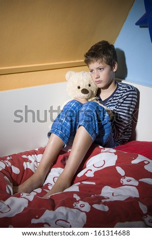 A young boy is sitting sad and depressed on his bed in his bedroom - stock photo