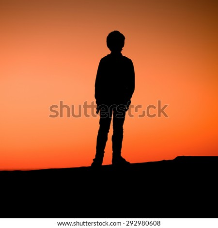 A young boy is standing on a pier enjoying the red sunset. Silhouette of a kid - stock photo