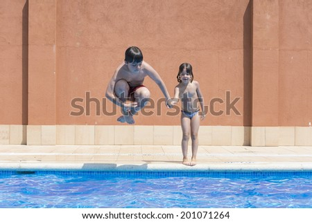a young boy jumping in pump in an outdoor pool while her sister jumps not making a joke - stock photo