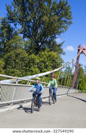 A young boy leads his mother as they ride their bicycles across the DeFazio Bike Bridge in Eugene Oregon. - stock photo