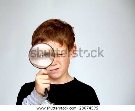 a young boy looks at You the Viewer while looking through a magnifying glass enlarging his eye - stock photo