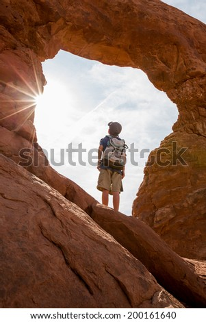 A Young Boy Looks Through a Natural Window in the Great Outdoors - stock photo
