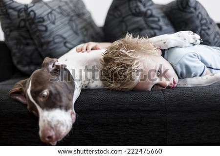 A young boy lying on the sofa with his big puppy. - stock photo