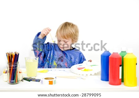 A young boy making a painting with poster paint
