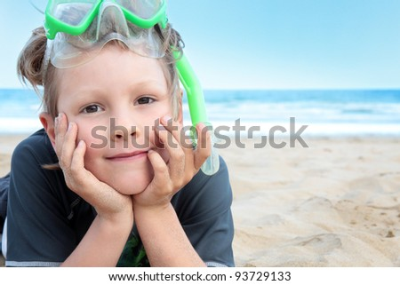 A young boy on the beach with his snorkeling equipment.
