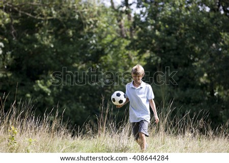 A young boy playing football in a field - stock photo