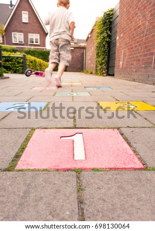 A young boy playing hopscotch in a playground