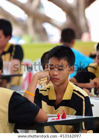 a young boy playing Thai chess, a type of chess playing in Thailand and surrounding nations, in a local chess competition in Khon Kaen Thailand September 2013