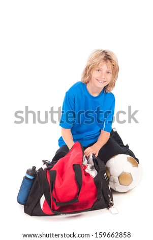 a young boy, ready for going to play football, with his sport bag and football
