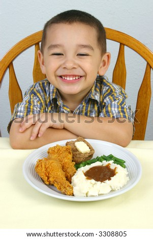 A young boy ready to eat his fried chicken dinner