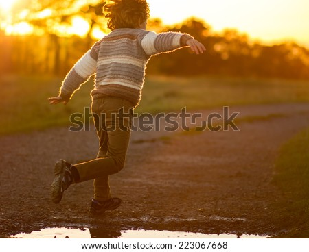a young boy running with arms outstretched jumping over a puddle at sunset - stock photo