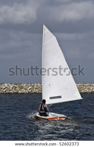 A young boy sailing on a small sail boat - stock photo
