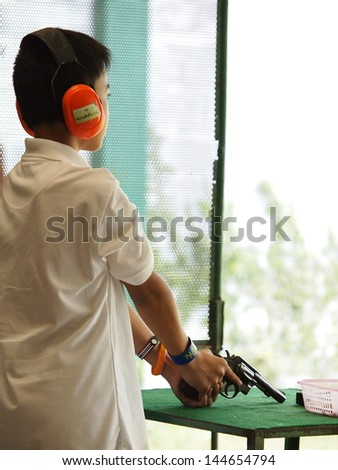 a young boy shooting to target with 0.38 S&W revolver - stock photo