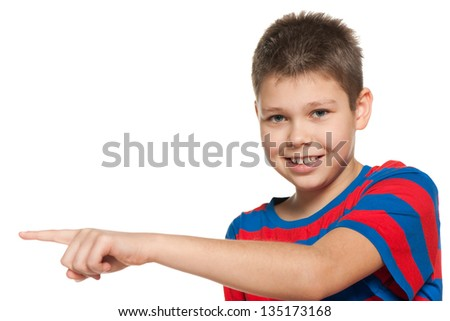 A young boy shows her finger to the side; on the white background - stock photo