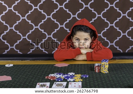 A young boy sitting at a poker table gambling playing cards with a brown background - stock photo
